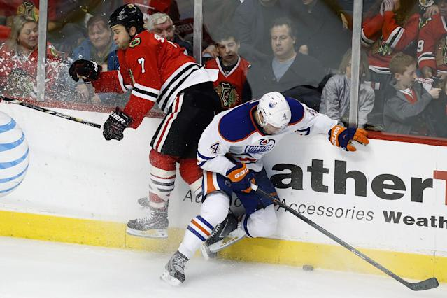 Chicago Blackhawks defenseman Brent Seabrook (7) and Edmonton Oilers left wing Taylor Hall (4) hit the glass over the puck during the second period of an NHL hockey game on Sunday, Nov. 10, 2013, in Chicago. (AP Photo/Andrew A. Nelles)