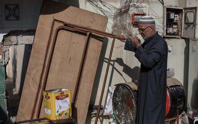 A man reveals one of the holes that ISIS fighters made residents construct to allow their fighters to pass unobserved through the neighbourhood of Samood, on the southern edge of western Mosul. - Credit: Sam Tarling / The Telegraph