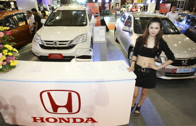 File Photo: A model stands next to a display of various Honda car models as customers check out one of the models during the four-day Manila International Auto Show. (AP Photo/Bullit Marquez, File)