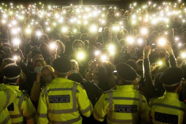 Members of the crowd shine lights from their phones at the vigil for Sarah Everard in March
