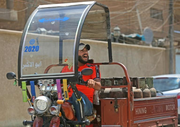 Deliveryman Mountazar Abbas announces the arrival of his cylinder-laden rickshaw by singing in the Karrada district of Iraq's capital Baghdad