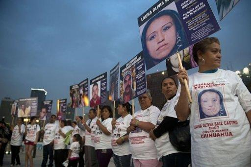 Mothers hold a banners with pictures of their sons and daughters at Revolution square in Mexico City