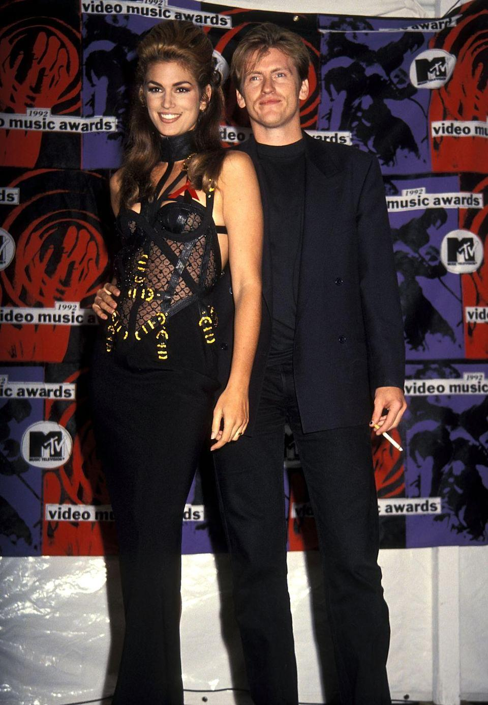 <p>Cindy Crawford sizzled in this strappy black gown with a see-through bodice at the 1992 show.</p>
