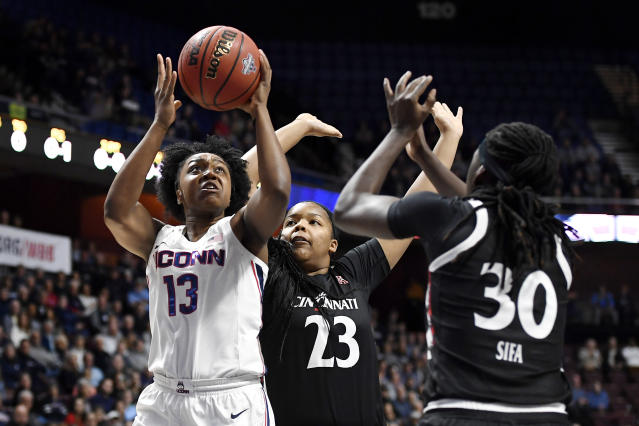Connecticut's Christyn Williams (13) shoots over Cincinnati's IImar'I Thomas (23) and Florence Sifa (30) during the first half of an NCAA college basketball game in the American Athletic Conference tournament finals at Mohegan Sun Arena, Monday, March 9, 2020, in Uncasville, Conn. (AP Photo/Jessica Hill)