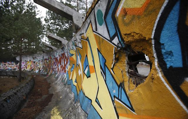 In this picture taken on Friday, Feb. 21, 2014, the bobsleigh track damaged by artillery fire is painted with graffiti at Mt. Trebevic near Bosnian capital of Sarajevo. Wartime destruction and negligence have turned most of Sarajevo's 1984 Winter Olympic venues into painful reminders of the city's golden times. The world came together in the former Yugoslavia in 1984 after the West had boycotted the 1980 Olympics in Moscow and Russia boycotted the 1984 Summer Games in Los Angeles. Just eight years later, the bobsleigh and luge track on Mount Trbevic was turned into an artillery position from which Bosnian Serbs pounded the city for almost four years. Today, the abandoned concrete construction looks like a skeleton littered with graffiti. (AP Photo/Amel Emric)