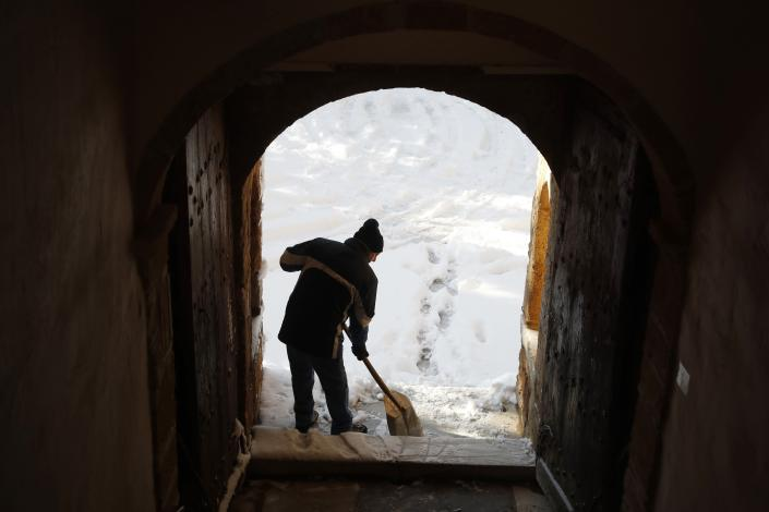 A worker clears the snow-covered entrance of Penteli Monastery in northern Athens, Tuesday, Jan. 8, 2019. Schools will remain closed across many parts of the country as a new cold weather front brings freezing temperatures and heavy snowfall. (AP Photo/Thanassis Stavrakis)