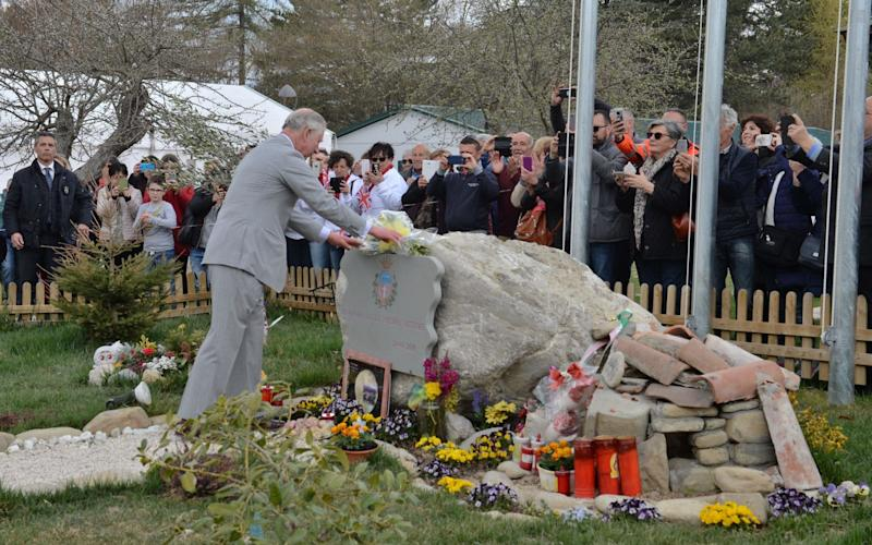 The Prince of Wales lays flowers at the earthquake memorial - Credit: John Stillwell/PA