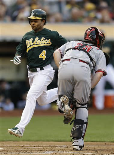Oakland Athletics' Coco Crisp (4) scores past Cincinnati Reds catcher Ryan Hanigan, right, in the third inning of a baseball game Tuesday, June 25, 2013, in Oakland, Calif. Crisp scored on a single by Yoenis Cespedes. (AP Photo/Ben Margot)