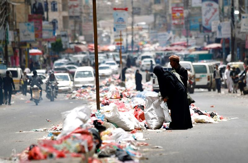 Yemenis salvage for discarded items in piles of rubbish lining a road in Sanaa on May 9, 2017 (AFP Photo/MOHAMMED HUWAIS)