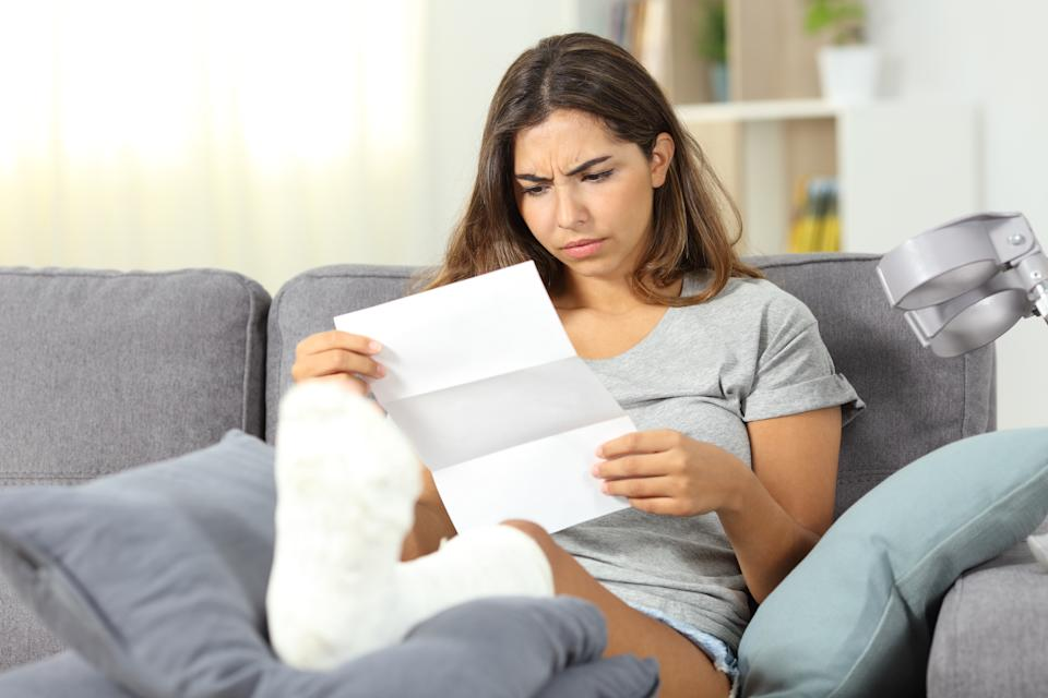Worried disabled woman reading a letter sitting on a couch in the living room at home
