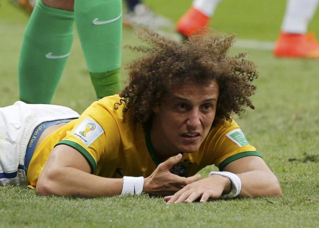 Brazil's David Luiz lies on the pitch after missing a goal during the 2014 World Cup third-place playoff between Brazil and the Netherlands at the Brasilia national stadium in Brasilia July 12, 2014. REUTERS/Ueslei Marcelino (BRAZIL - Tags: TPX IMAGES OF THE DAY SOCCER SPORT WORLD CUP)