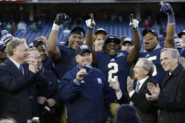 New York Yankees president Randy Levine, left, reacts along with Yankees chief operating officer Lonn Trost, second from right, and Rev. John I Jenkins, President of the University of Notre Dame, right, as Notre Dame head coach Brian Kelly speaks after the Pinstripe Bowl NCAA college football game against Rutgers Saturday, Dec. 28, 2013, at Yankee Stadium in New York. Notre Dame won the game 29-16. (AP Photo/Frank Franklin II)