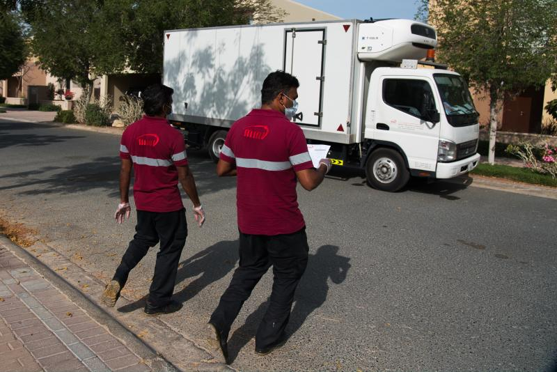 In this Tuesday, April 7, 2020 photograph, deliverymen leave after dropping off alcohol at a home in Dubai, United Arab Emirates. Dubai's two major alcohol distributors have partnered to offer home delivery of beer, spirits and wine as the new coronavirus now threatens a crucial source of tax and general revenue for the rulers of this Islamic city-state. The decision marks yet another loosening of social mores in the skyscraper-studded desert metropolis. (AP Photo/Jon Gambrell)