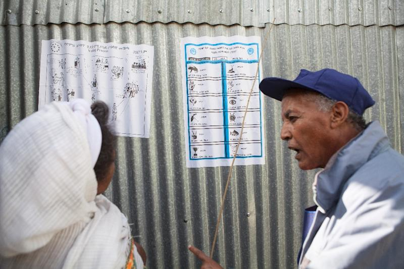 An Ethiopian Electoral Board employee explains the voting process to a voter at a polling station in Addis Ababa on May 24, 2015 (AFP Photo/Zacharias Abubeker)