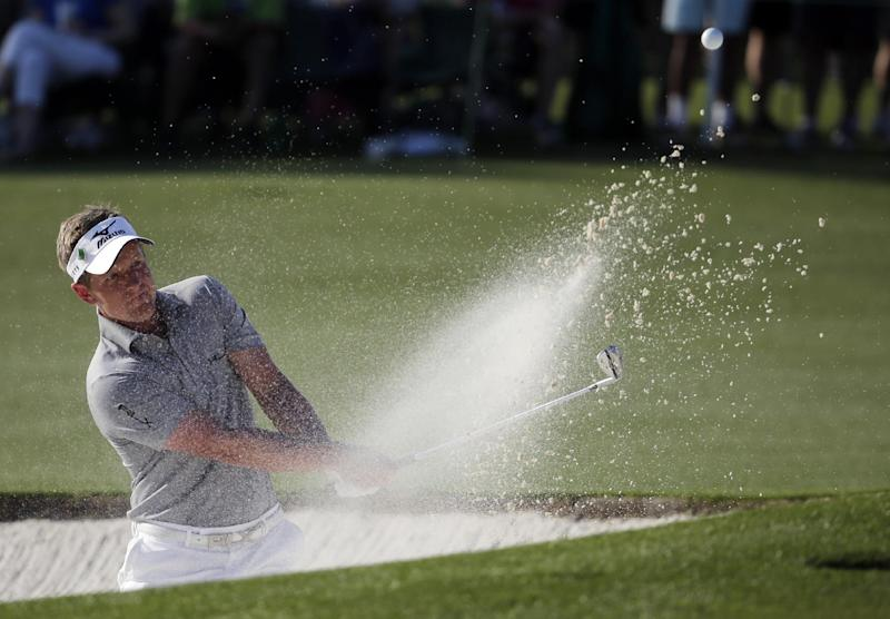 Luke Donald, of England, hits out of a bunker on the 17th hole during the first round of the Masters golf tournament Thursday, April 10, 2014, in Augusta, Ga