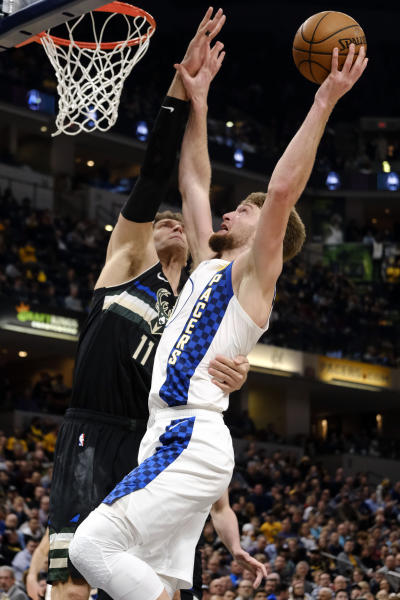 Indiana Pacers forward Domantas Sabonis, right, is fouled by Milwaukee Bucks center Brook Lopez during the first half of an NBA basketball game in Indianapolis, Wednesday, Feb. 12, 2020. (AP Photo/AJ Mast)