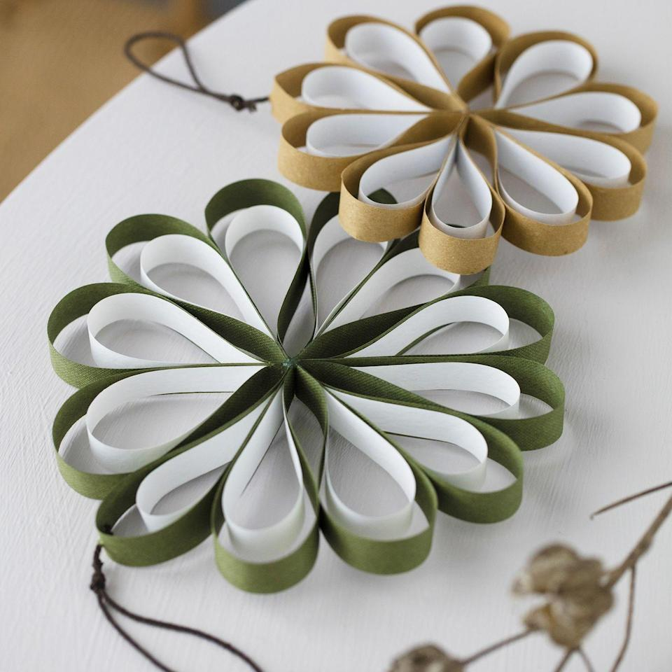 <p>Create your own paper decorations: cut 12 strips each from white and coloured thick paper, making coloured strips slightly longer. Glue the ends of the white strips together, then attach the coloured ones to them. Fix the bows together with a glue fun. Add a thread so they can be easily hung.</p>