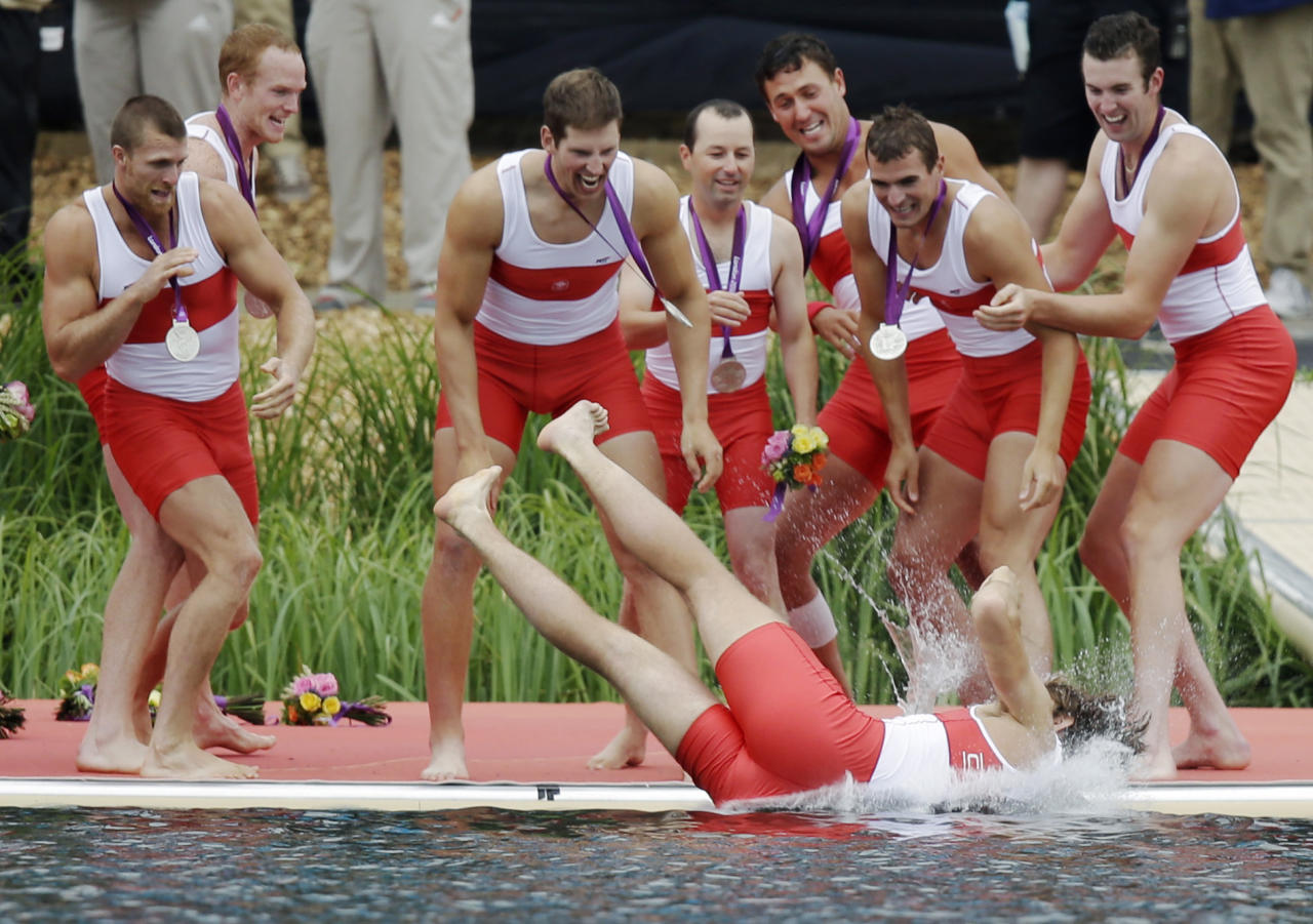 Members of Canada's men's rowing eight throw a teammate in Lake Dorney after winning the silver medal in Eton Dorney, near Windsor, England, at the 2012 Summer Olympics, Wednesday, Aug. 1, 2012. (AP Photo/Natacha Pisarenko)