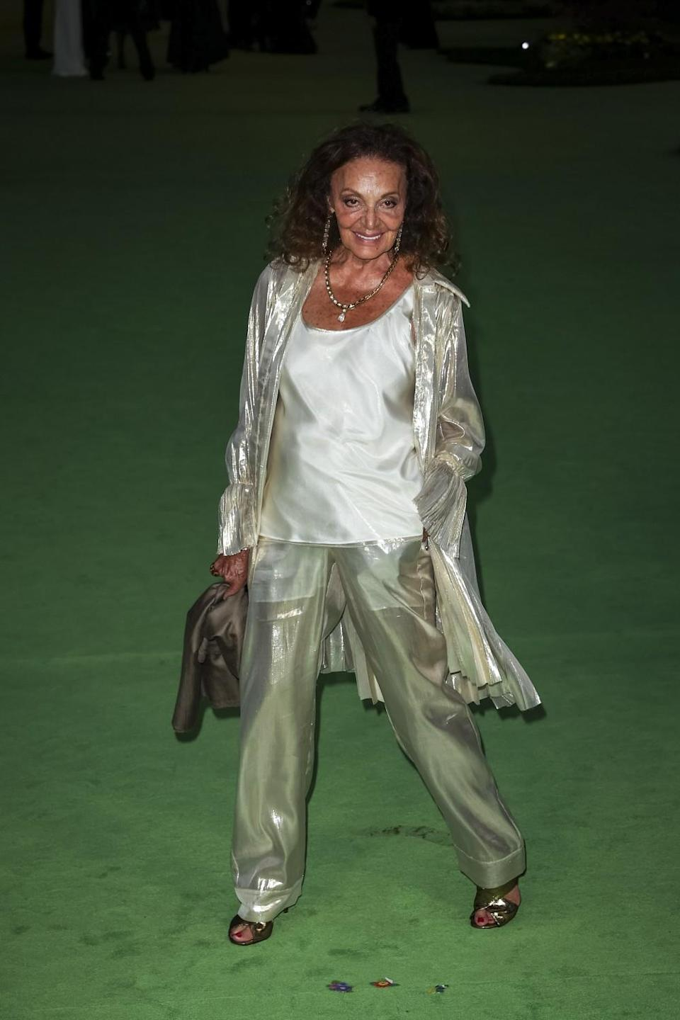 A woman in a silver suit posing on a green carpet