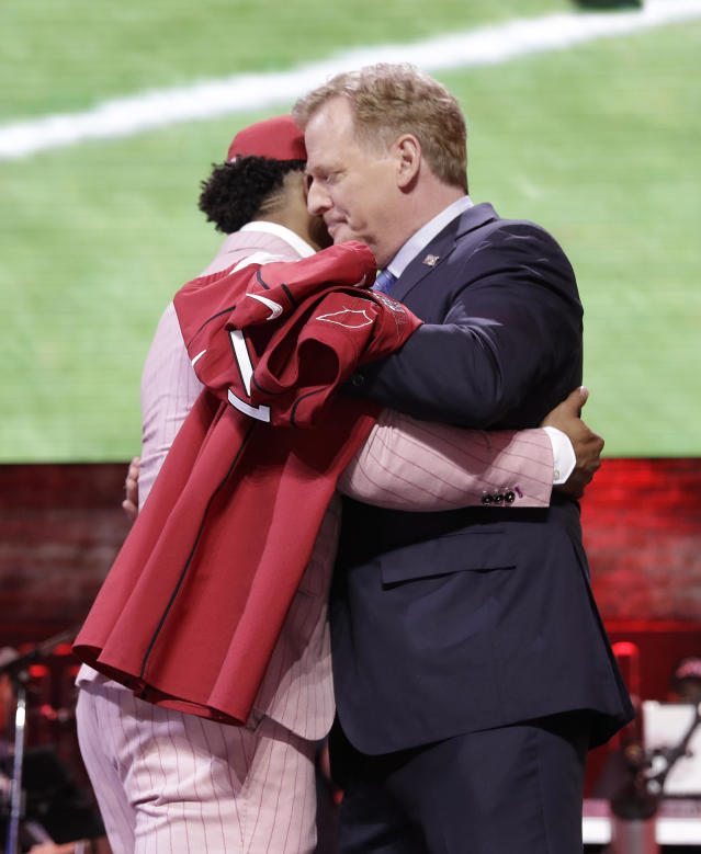 """FILE - In this April 25, 2019, file photo, Oklahoma quarterback Kyler Murray embraces NFL Commissioner Roger Goodell after the Arizona Cardinals selected Murray in the first round at the NFL football draft in Nashville, Tenn. NFL vice president Troy Vincent has sent a letter to several prospects inviting them to participate """"live"""" in the NFL draft in three weeks. In recent drafts, first-round selections were announced by Commissioner Goodell. Then followed hugs involving players and Goodell — some of them comical — and photo sessions with the players wearing team ball caps or even showing off team jerseys. This year, with all public events at the planned site of Las Vegas canceled and the draft set to proceed remotely, players will likely be at their homes when their names are called. (AP Photo/Mark Humphrey, File)"""