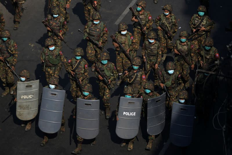 Myanmar soldiers walk along a street during a protest against the military coup in Yangon