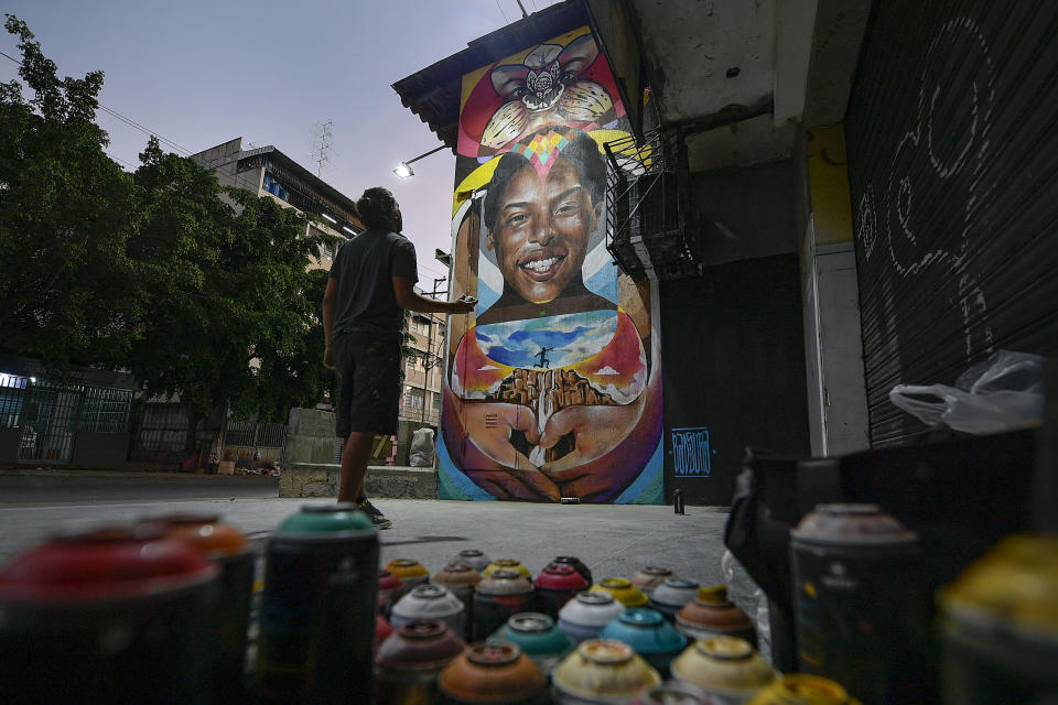 "Street artist Wolfgang Salazar studies his mural honoring Venezuelan athlete Yulimar Rojas as he adds finishing touches, in the Boleita neighborhood of Caracas, Venezuela, Monday, Jan. 11, 2021. Salazar has gained increasing fame for his spray-painted murals of Venezuelans at a time when the pandemic and economic hardship weigh upon his fellow citizens. ""I want people to smile for a moment,"" said the 30-year-old Salazar. ""I want them to go home with a different kind of story to tell."" (AP Photo/Matias Delacroix)"