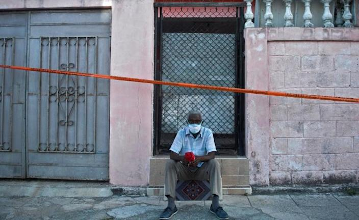 A man sits outside his home in a cordoned-off area of Havana after cases of Covid-19 were detected there