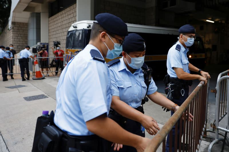 Police stand guards as a prison van arrive High Court on the first day of trial of Tong Ying-kit, the first person charged under a new national security law, in Hong Kong