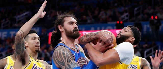 Steven Adams of the Oklahoma City Thunder (center) battles against the Los Angeles Lakers' Anthony Davis (right).