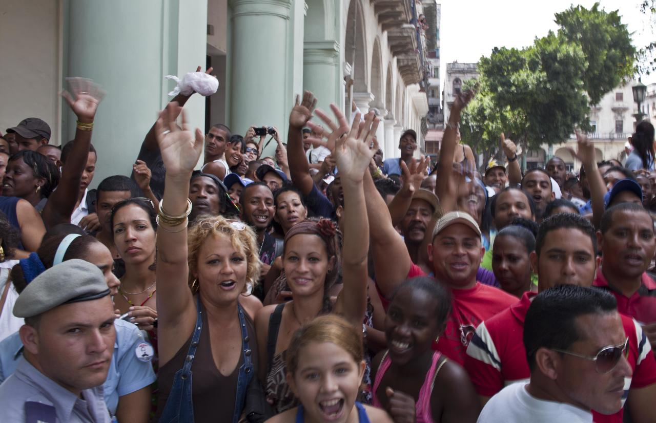 People react to the press as they wait outside the Saratoga hotel to see U.S. singer Beyonce in Old Havana, Cuba, Thursday, April 4, 2013. Beyonce is in Havana with her husband, rapper Jay-Z, on their fifth wedding anniversary. (AP Photo/Ramon Espinosa)