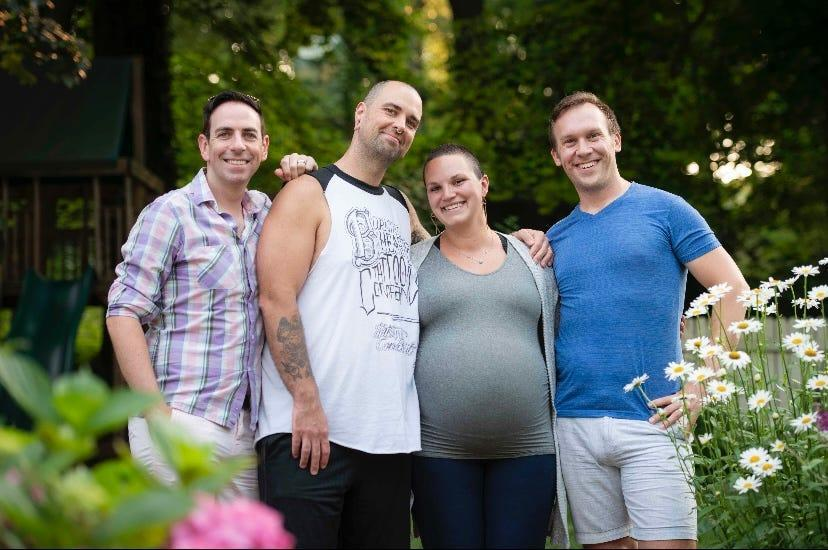 Maureen Farris (center) shown with her husband Jeremiah Currier (second from left) was the surrogate for three identical girls for new dads Kevin O'Neill (left) and Eric Portenga (right).