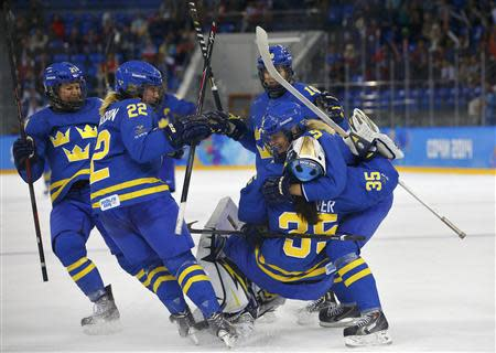 Sweden's women's ice hockey players celebrate after defeating Finland in their women's ice hockey playoffs quarter-final game at the Sochi 2014 Winter Olympic Games