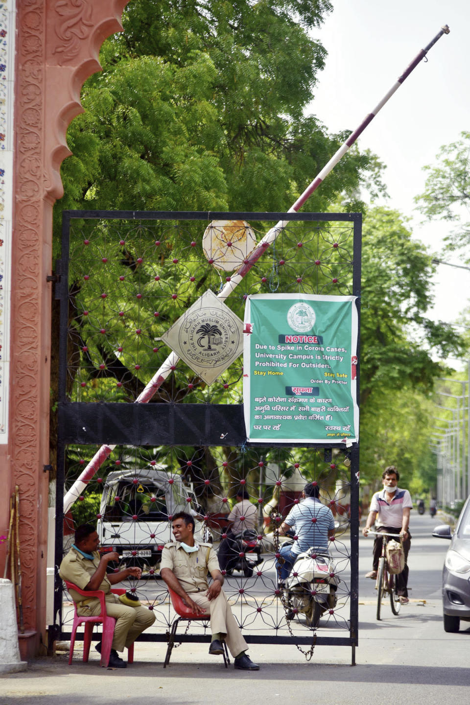 Policemen sit at the entrance of Aligarh Muslim University (AMU) with a banner announcing its closure because of the coronavirus pandemic in Aligarh, India, Saturday, June 12, 2021. Within just one month, the official Facebook page of Aligarh Muslim University, one of the topmost in India, published about two dozen obituaries of its teachers, all lost to the pandemic. Across the country, the deaths of educators during the devastating surge in April and May have left students and staff members grief-stricken and close-knit university communities shaken. (AP Photo/Manoj Aligadi)