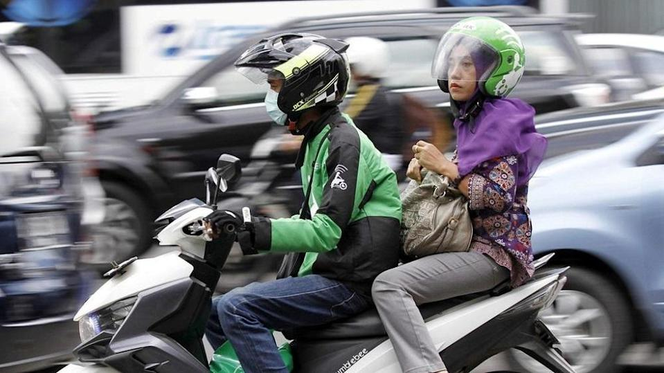A women uses the Go-Jek service in Jakarta. — Reuters file pic