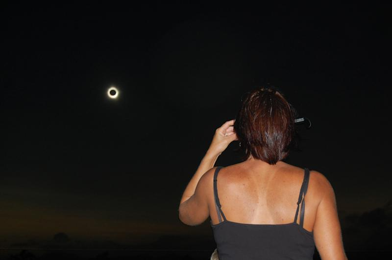 In this photo provided by Tourism Queensland, a woman watches a total solar eclipse at Lakeland in Queensland state, Australia, Wednesday, Nov. 14, 2012. Starting just after dawn, the eclipse cast its 150-kilometer (95-mile) shadow in Australia's Northern Territory, crossed the northeast tip of the country and was swooping east across the South Pacific, where no islands are in its direct path. (AP Photo/Tourism Queensland, David Barker) EDITORIAL USE ONLY