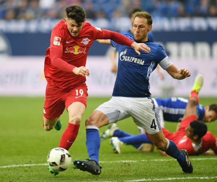Schalke's defender Benedikt Hoewedes and Leipzig's midfielder Oliver Burke fight for the ball on April 23, 2017
