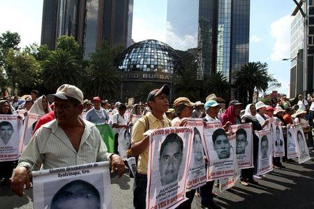 Relatives carry photos of some of the 43 missing students of the Ayotzinapa teachers' training college during a march to mark the ten-month anniversary of their disappearance, in Mexico City