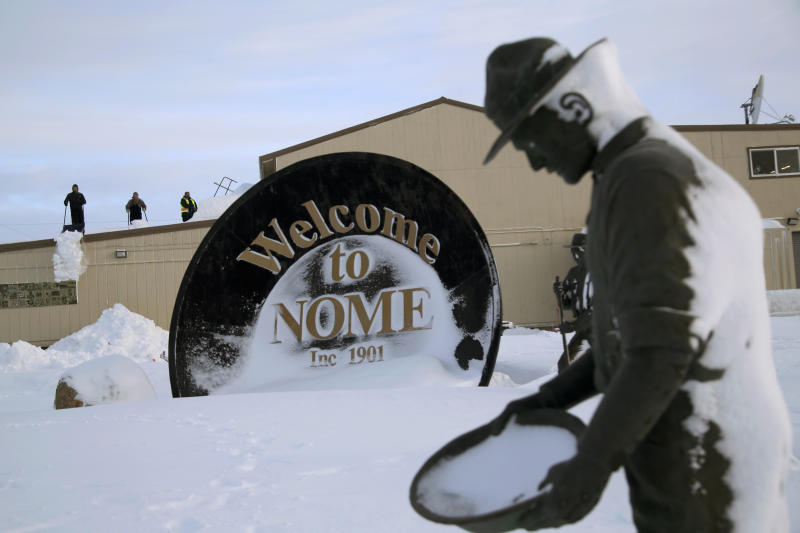 """In this Feb. 14, 2019, photo, three men shovel snow off the roof of a grocery store while in the foreground, a statue of one of the """"Three Lucky Swedes"""" credited with discovering gold in the late 19th century in Nome, Alaska. The city later added statues of two native boys who led them to find the gold. (AP Photo/Wong Maye-E)"""