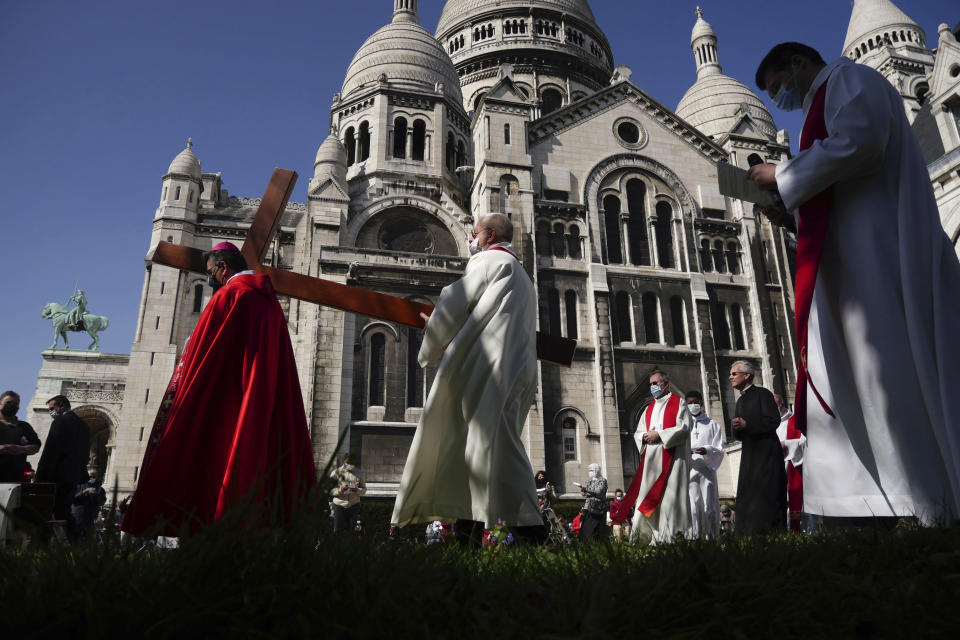 Paris Archbishop Michel Aupetit, left, carries a cross at the Way of the Cross ceremony as part of the Holy Easter celebration, in the Sacre Coeur basilica, in Paris, Friday, April 2, 2021. In France, a nationwide 7 p.m. curfew is forcing parishes to move Good Friday ceremonies forward in the day, as the traditional Catholic night processions are being drastically scaled back or cancelled. (AP Photo/Thibault Camus)