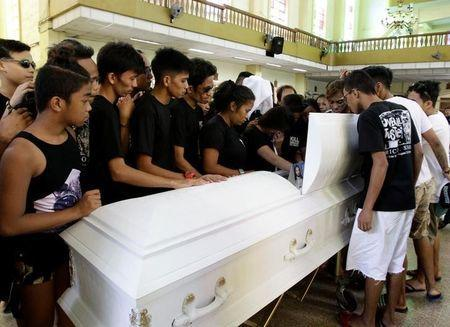 Relatives and friends look at the coffin of Eric Quintinita Sison during burial rites in Pasay city, metro Manila, Philippines August 31, 2016. Picture taken August 31, 2016. REUTERS/Czar Dancel
