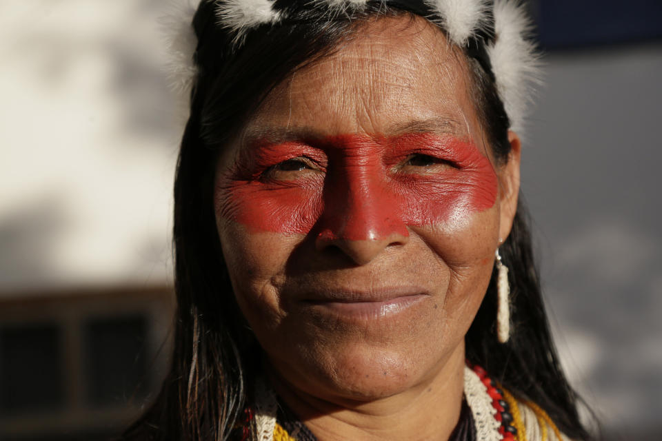 A Waorani woman smiles as she marches with others to a courthouse to attend the ruling on a lawsuit filed by the Waoranis against the Ministry of Non-Renewable Natural Resources for opening up oil concessions on their ancestral land, in Puyo, Ecuador, Friday, April 26, 2019. The judge went on to rule in favor of the Waoranis. (AP Photo/Dolores Ochoa)