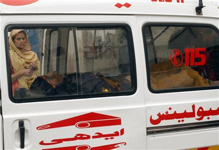 A woman, who was injured by unidentified gunmen, lies in an ambulance after being brought to the Civil Hospital for treatment in Karachi March 12, 2014. REUTERS/Athar Hussain