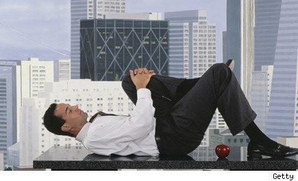 man in a business suit performs stretches on his desk