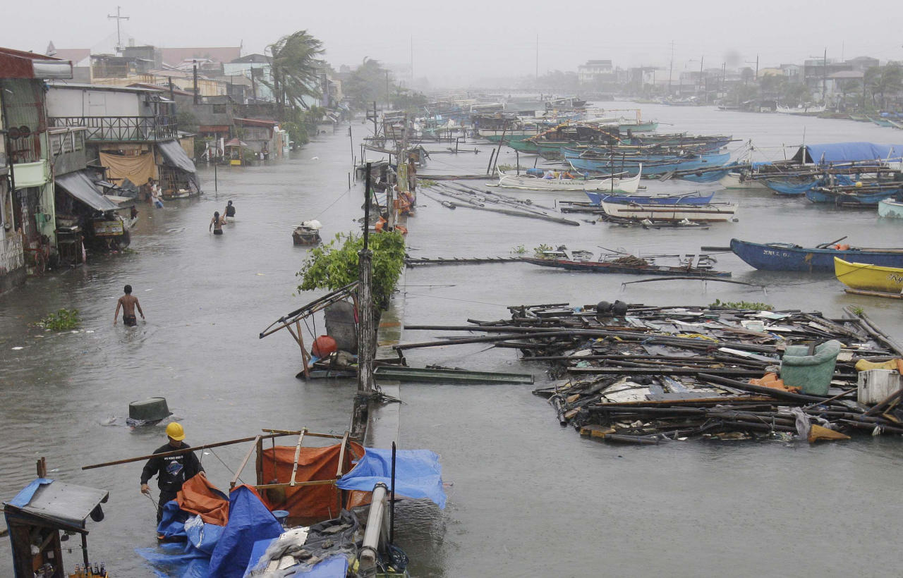 In this Sept. 27, 2011 file photo, people walk along a flooded street in Navotas, north of Manila, Philippines, as Typhoon Nesat hits the country. Like most of monsoon-swept Asia, the city and its environs have experienced periodic floods since it was founded more than two centuries ago. But recent decades have witnessed dramatic changes - from intense urbanization to rising waters blamed on climate change - that are turning once burdensome but bearable events into national crises. (AP Photo/Aaron Favila, File)