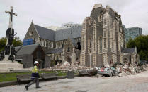 FILE - In this Feb. 26, 2011, file photo, a relief worker walks past the earthquake-damaged Christ Church Cathedral in Christchurch, New Zealand. The Christ Church Cathedral was arguably New Zealand's most iconic building before much of it crumbled during an earthquake 10 years ago. The years of debate that followed over whether the ruins should be rebuilt or demolished came to symbolize the paralysis that has sometimes afflicted the broader rebuild of Christchurch. But as the city on Monday, Feb. 22, 2021 marks one decade since the quake struck, killing 185 people and upending countless more lives, there are finally signs of progress on the cathedral. It's being rebuilt to look much like the original that was finished in 1904, only with modern-day improvements to make it warmer and safer. (AP Photo/Mark Baker, File)