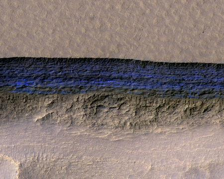 NASA handout photo of a cross-section of a thick sheet of underground ice in this enhanced-color view of Mars