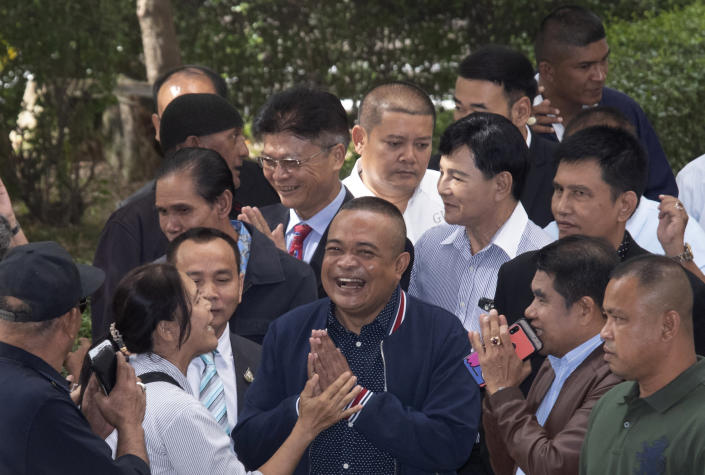 Jatuporn Phromphan, front center, one of the leaders of Red Shirt, talks to his supporters on his arrival at the Bangkok Criminal Court in Bangkok, Thailand, Wednesday, Aug. 14, 2019. The court has dismissed charges of terrorism and other offenses against 24 leaders of an extended street protest in 2010 that saw key parts of central Bangkok closed off and random violence that was ended by armed military force. (AP Photo/Sakchai Lalit)