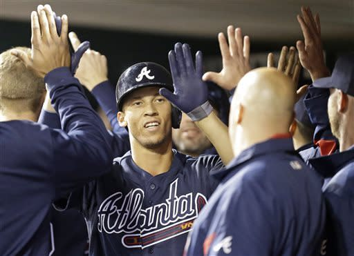 Atlanta Braves' Andrelton Simmons is congratulated in the dugout after hitting a two-run home run off Cincinnati Reds relief pitcher Logan Ondrusek in the eighth inning of a baseball game, Monday, May 6, 2013, in Cincinnati. Atlanta won 7-4. (AP Photo/Al Behrman)