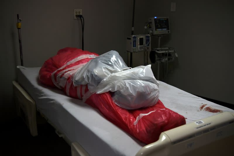 FILE PHOTO: A man who died from the coronavirus disease (COVID-19) is seen wrapped in a body bag in Houston
