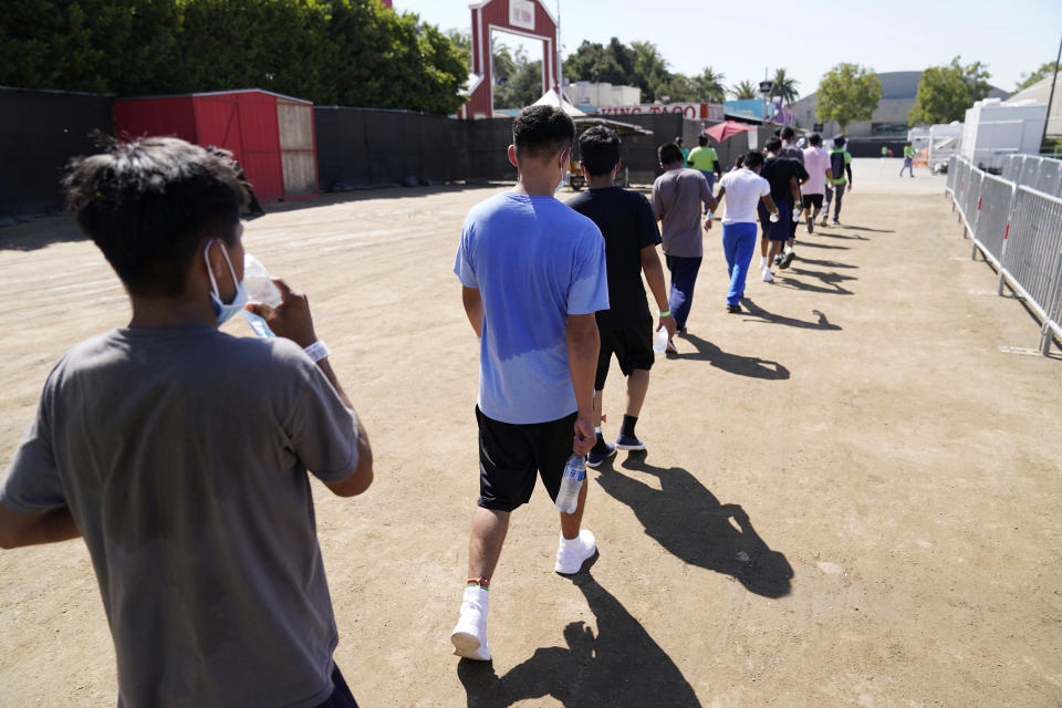 Children walk together after a game of soccer at an emergency shelter for migrant children Friday, July 2, 2021, in Pomona, Calif. The Biden administration on Friday gave a rare look inside the emergency shelter it opened to house migrant children crossing the U.S.-Mexico border alone, calling the California facility a model among its large-scale sites, some of which have been plagued by complaints. (AP Photo/Marcio Jose Sanchez, Pool)